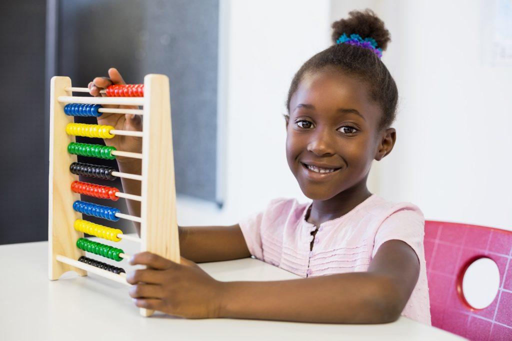 Schoolgirl using a maths abacus in classroom
